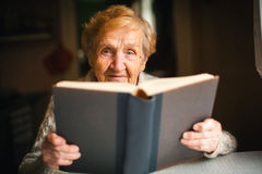 Elderly woman reading a book. Stock Photos