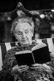 Elderly only woman reading a book sitting in a hammock. Stock Image