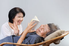 Elderly woman reading fable book with daughter Stock Image