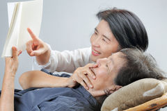 Elderly woman reading fable book with daughter Royalty Free Stock Photos