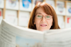 Elderly woman reading newspaper in library Stock Photo