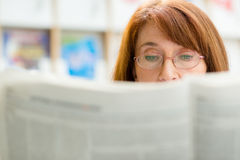 Elderly woman reading newspaper in library Royalty Free Stock Photo