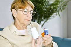 Elderly woman reading pill bottles Stock Photos