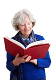 Elderly woman reading red book Royalty Free Stock Photos