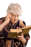 Elderly woman reads the book Stock Photos