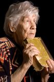 Elderly woman reads the book Stock Image