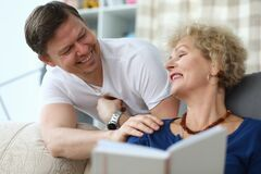 Elderly woman reads book at home, next adult son