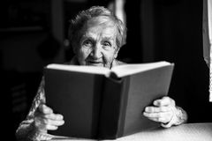 An elderly woman reads the book sitting at the table. Black and white portrait Stock Image