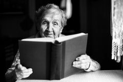 Elderly woman reads the book at the table. Black-and-white photo Stock Images