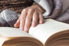An elderly woman reads a book. The woman`s hand lies on an open royalty free stock images