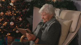 Elderly woman reads mails on the tablet stock video footage
