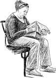 Elderly woman reads a newspaper Royalty Free Stock Photo