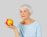 Elderly woman with red apple in hands on a light background Stock Photos
