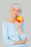Elderly woman with red apple in hands on a light background Royalty Free Stock Image