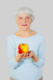 Elderly woman with red apple in hands on a light background Royalty Free Stock Photos