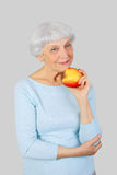 Elderly woman with red apple in hands on a light background in t Stock Photos