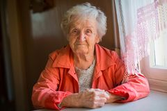 Elderly woman in red jacket sitting at table . Royalty Free Stock Photography