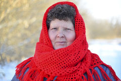 Elderly woman in red knitted scarf on her head Stock Photography