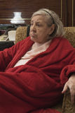 Elderly woman in red robe relaxing in a chair Stock Photo
