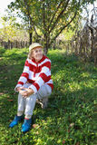 Elderly woman relaxes on a chair in the grass Stock Photography