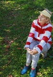 Elderly woman relaxes on a chair in the grass Stock Images