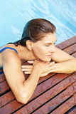 Elderly woman relaxing at pool edge Stock Images