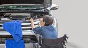 Elderly woman repairing her car Royalty Free Stock Photos