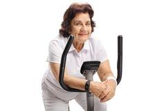 Elderly woman resting on an exercise bike Stock Photos