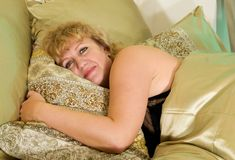Elderly woman rests in bed Stock Photos