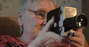 Elderly woman with retro camera at home stock video footage