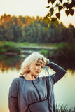 Elderly woman at the river. Beautiful mature woman standing in front of the river in autumn Royalty Free Stock Image