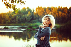 Elderly woman at the river. Beautiful mature woman standing in front of the river in autumn Royalty Free Stock Photography