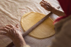 Elderly woman rolling out dough Royalty Free Stock Photos