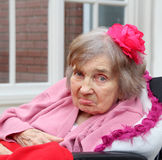 Elderly woman with rose in hair. Photo of a disabled elderly woman with a red rose fascinator in her hair Royalty Free Stock Photos