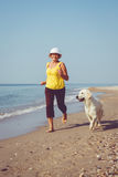 Elderly woman running with her golder retriever. Happy elderly woman running along a beach with her golden retriever at the morning royalty free stock photography