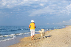 Elderly woman running with her golder retriever. Happy elderly woman running along a beach with her golden retriever at the morning, back view royalty free stock image