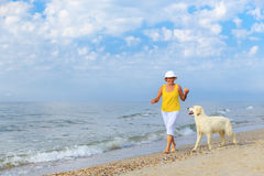 Elderly woman running with her golder retriever Stock Images