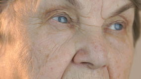 Elderly woman`s face with tired expression of face stock footage