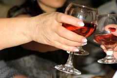 Elderly woman`s hand with a glass of wine reaching for another glass royalty free stock image