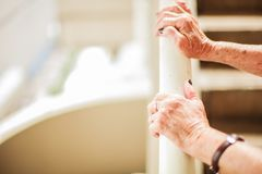 Elderly woman`s hands climbing stair using handrail with copy space, white background.  royalty free stock photo