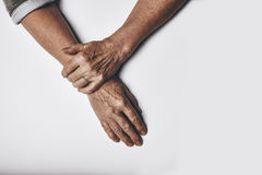Elderly woman's hands on grey background Royalty Free Stock Photography