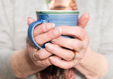 Elderly woman`s hands holding a hot drink Royalty Free Stock Photo