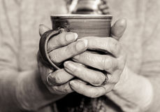 Elderly woman`s hands holding a hot drink. Monochrome. Stock Photography