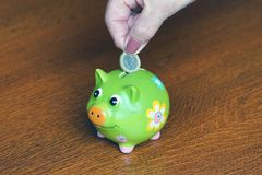 Elderly woman saves money. Close-up of senior woman hand putting coin into piggy bank. stock photography