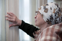 Elderly woman in scarf and glasses. Lonely grandma in scarf and glasses looking aside royalty free stock photo