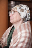 Elderly woman in scarf and glasses. Lonely grandma in scarf and glasses looking aside stock photos
