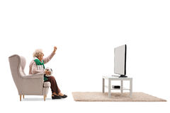 Elderly woman seated in an armchair watching soccer on TV Royalty Free Stock Images