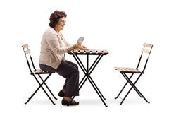 Elderly woman seated at a table playing cards stock photography