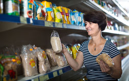 Elderly woman selecting groats at grocery store Stock Images