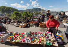 Elderly woman selling handmade toys on outdoor market during city festival Stock Images